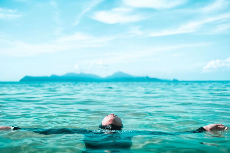 Teenage Girl Swimming In Sea Against Sky