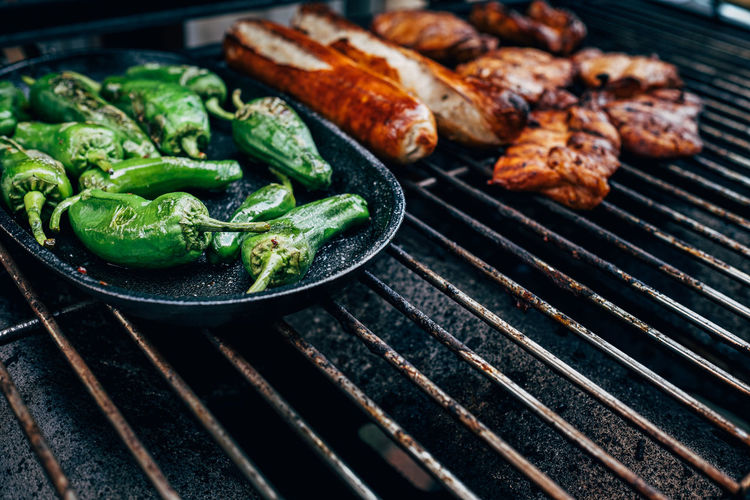 Close up of pimientos de padron on barbecue grill