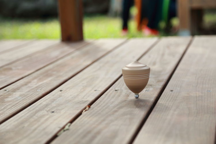 Close-up of spinning top on floorboard