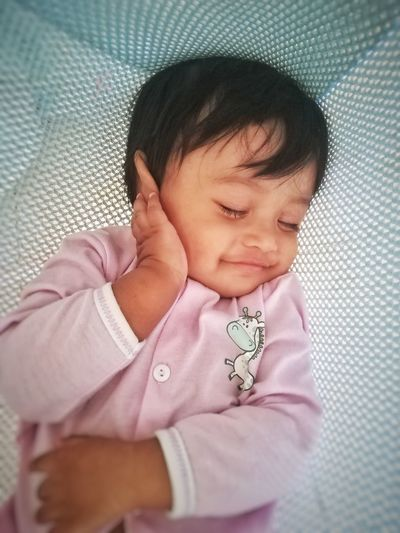 High angle view of cute baby boy sleeping in crib