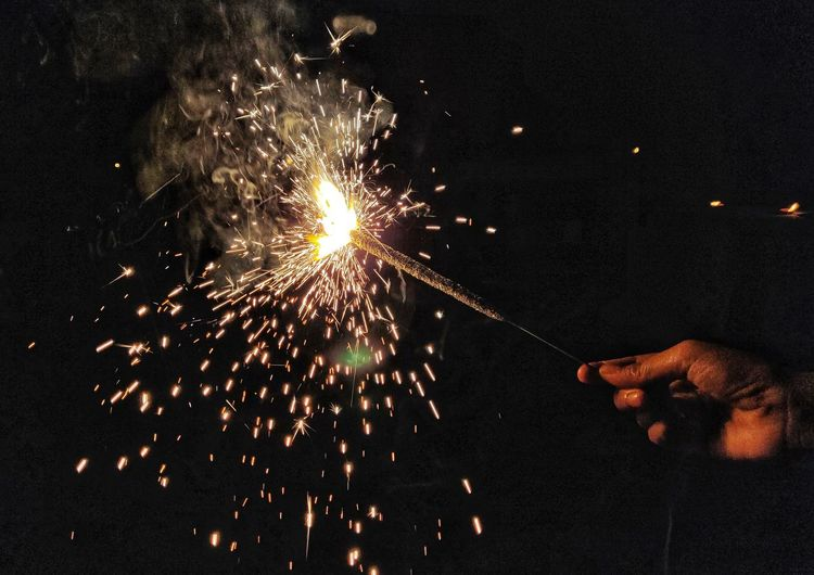 Cropped hand of person holding illuminated sparkler at night