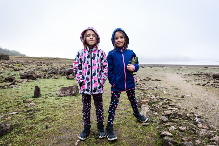 Portrait of sisters standing on field against sky