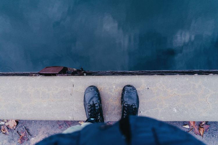 Low section of person wearing boots standing by water