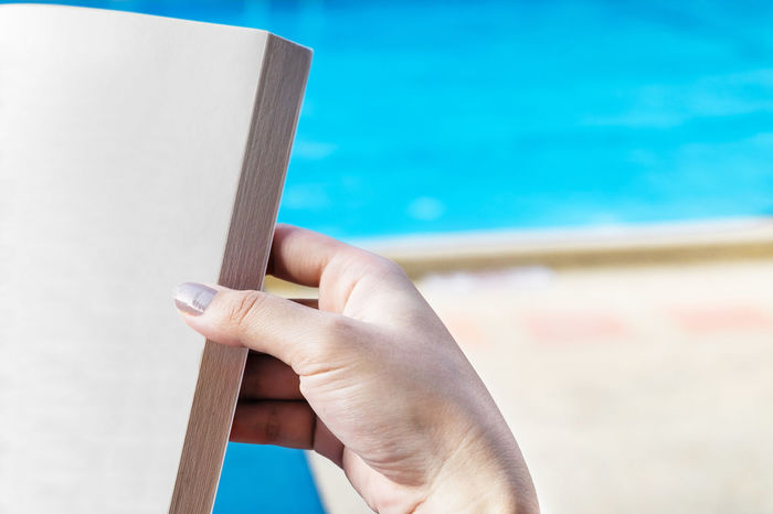 Woman reading near swimming pool with copy space. Background Blue Book Business Close-up Concept Copy Space Cropped Day Education Focus On Foreground Holding Human Finger Lifestyles Part Of Person Personal Perspective Reading Relaxing Resort Selective Focus Studying Success