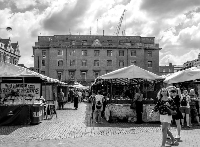 People on street market in city against sky