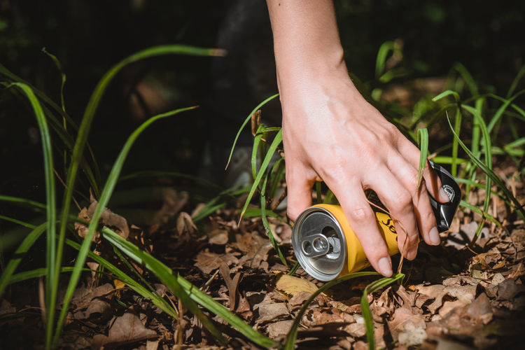 Environment concept, hand reaches for a metal can lying in the forest. environmental protection