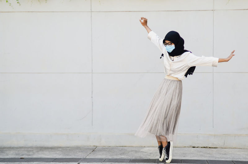 Full length of woman standing against white wall