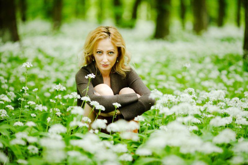 Portrait Of Beautiful Woman Sitting Amidst Flowering Plants At Park