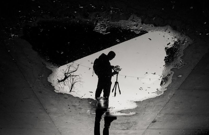 High angle view of man reflecting on puddle