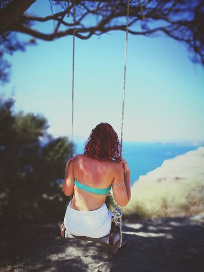Rear view of young woman swinging at park against clear sky
