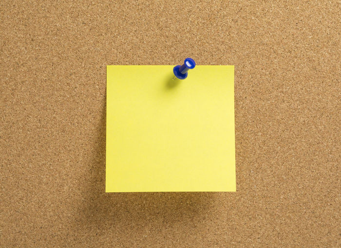 Close-up of blank yellow adhesive note on bulletin board