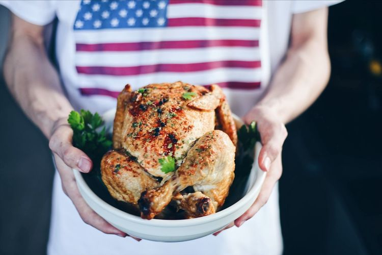 Midsection of man holding roasted chicken meat in bowl at home