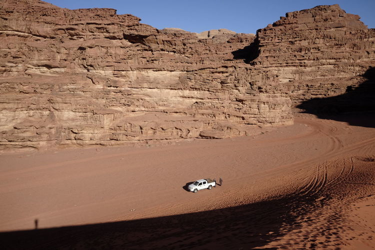 High Angle View Of Off-Road Vehicle At Desert Against Mountains