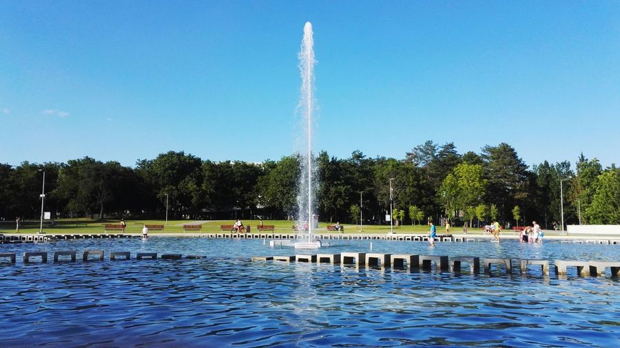 Fountain Splashing Water At Park Against Sky