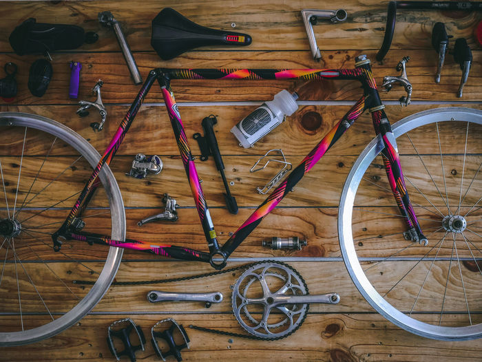 High Angle View Of Bicycle Parts On Hardwood Floor