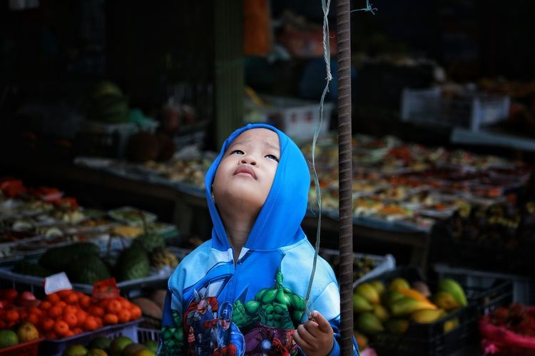 Boy standing amidst food at market stall