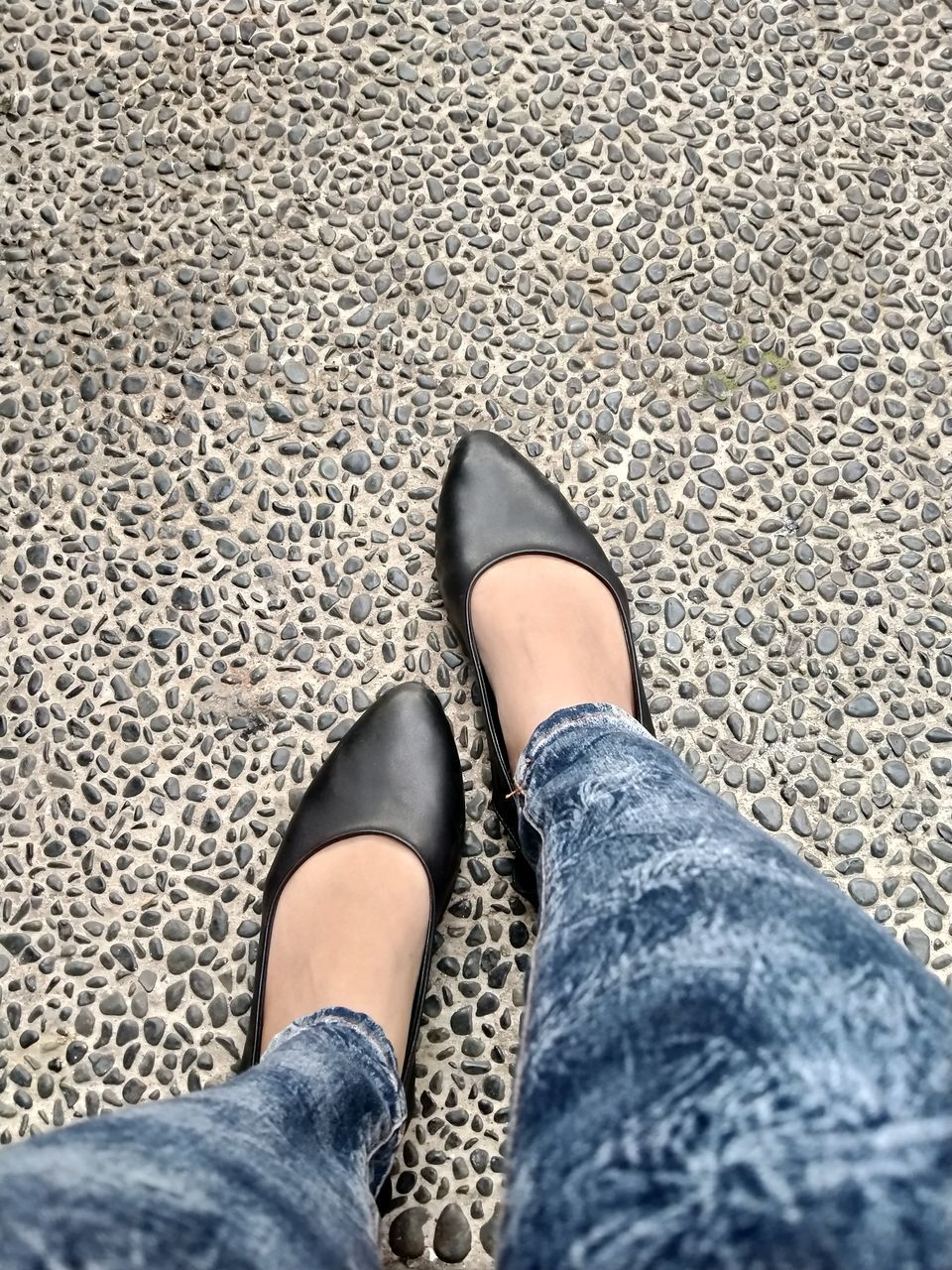 LOW SECTION OF WOMAN WEARING SHOES STANDING ON GROUND