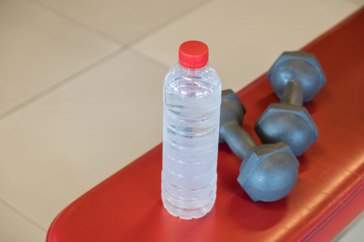 High angle view of bottle and dumbbell on table