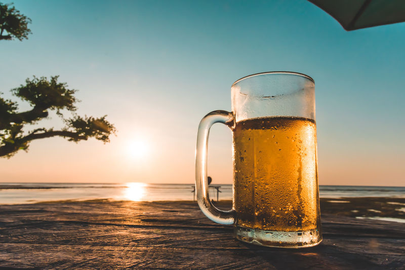 Beer glass on table against sea during sunset