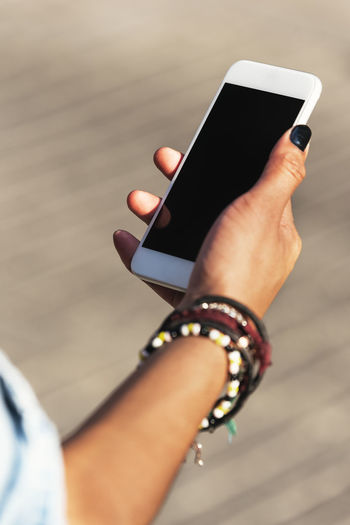 Cropped Hand Of Young Woman Using Smart Phone