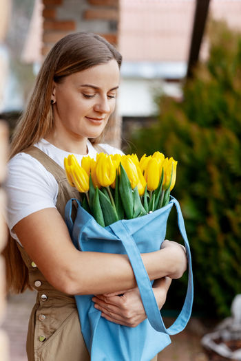 Portrait of a happy female florist with a bouquet of yellow tulips. women's day, valentine's day
