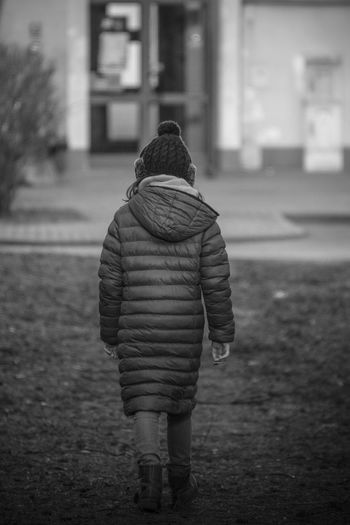 Rear View Of Girl Walking On Field During Winter