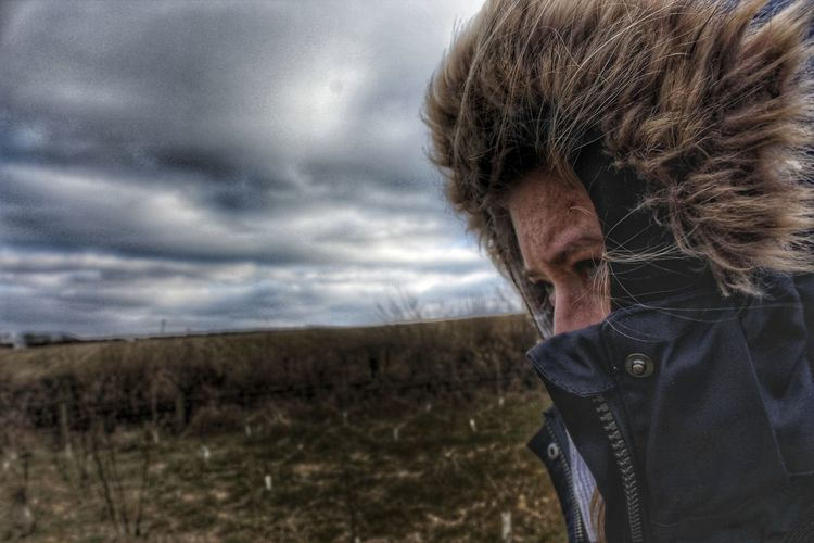 Close-Up Of Woman In Hooded Jacket Against Cloudy Sky