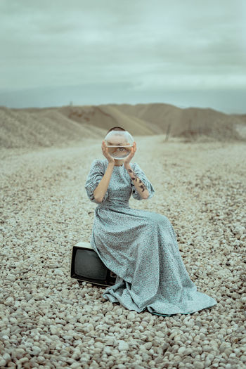 Portrait of woman holding fish bowl while sitting on field against cloudy sky