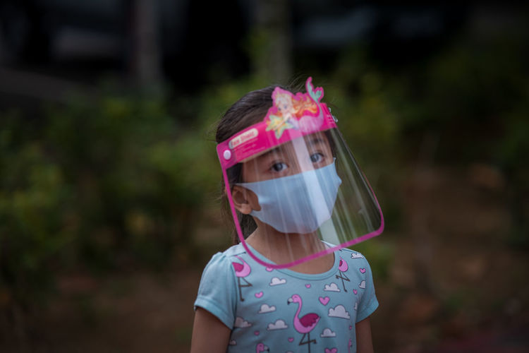 Portrait of cute girl wearing face mask standing outdoors