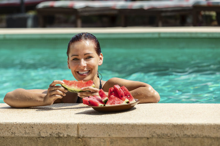 Young woman eating watermelon in the pool Water Swimming Pool Pool One Person Wellbeing Food Food And Drink Leisure Activity Nature Outdoors Looking At Camera Day Focus On Foreground Real People Lifestyles Portrait Smiling Watermelon Eating Plate Mallorca Mediterranean