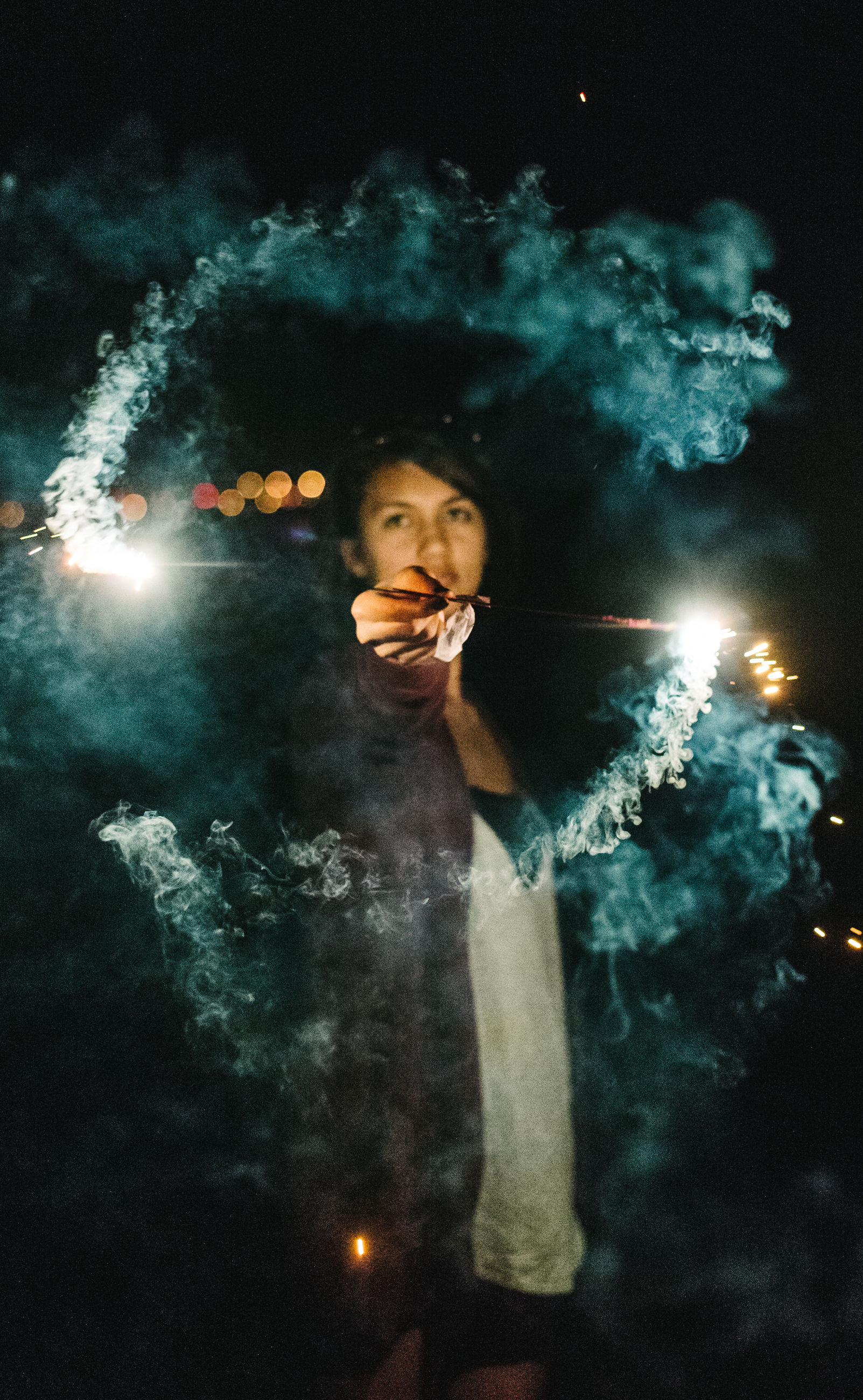 real people, smoke - physical structure, one person, looking at camera, night, leisure activity, burning, underwater, firework, lifestyles, portrait, firework display, flame, illuminated, holding, firework - man made object, young adult, indoors, young women, water, sky, close-up, undersea