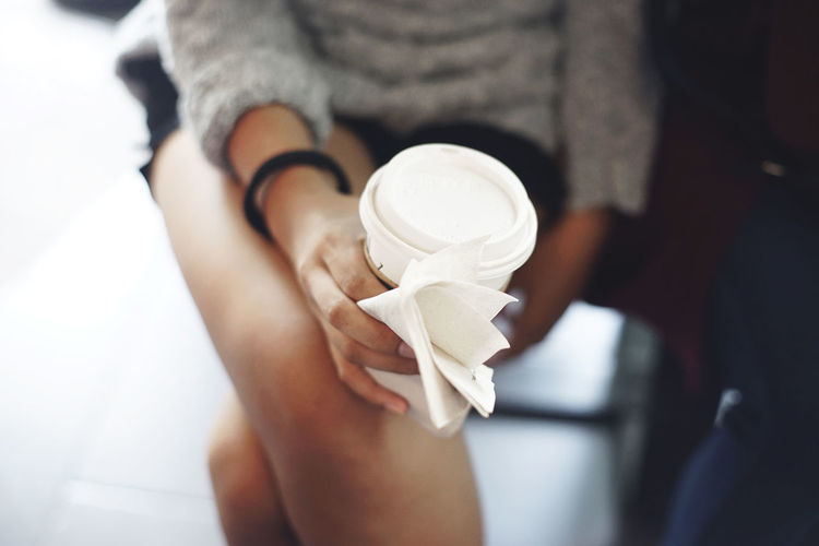 Midsection of woman holding disposable cup and tissue paper