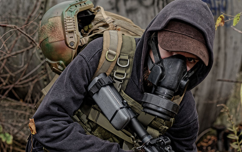 Portrait of man with sniper wearing gas mask