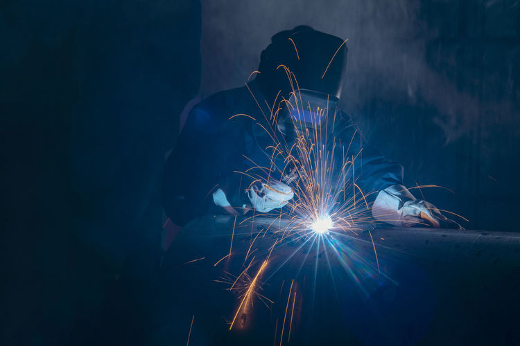 Man welding metal in workshop
