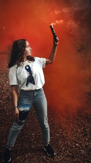 Full length of young woman holding distress flare outdoors