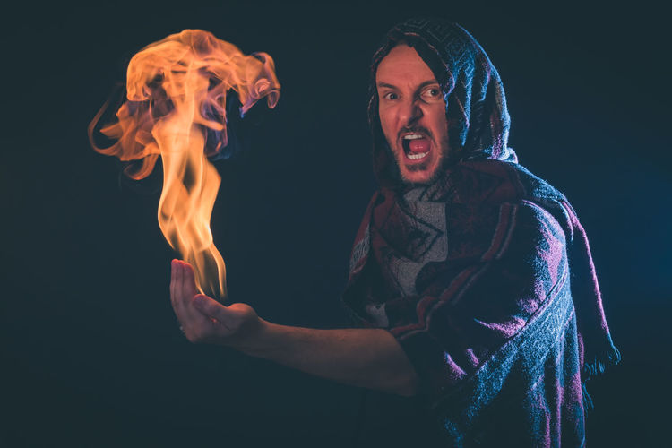 Portrait of shouting man holding fire against black background