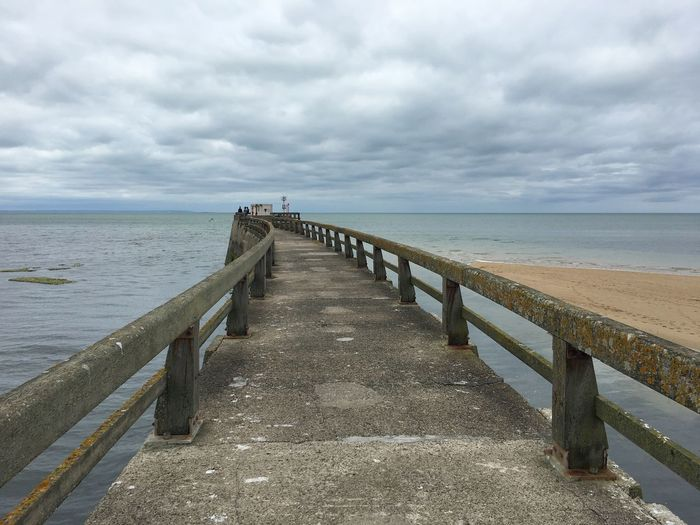View of pier leading to calm sea against cloudy sky