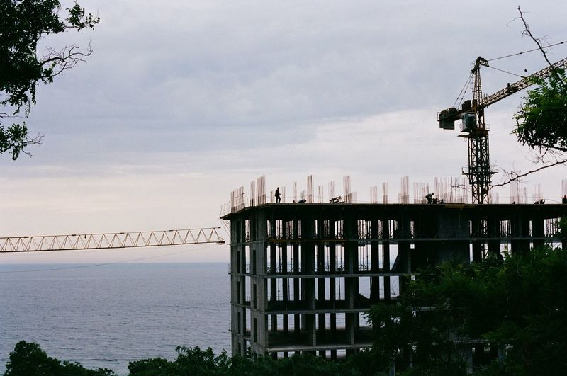 Built structure by sea against sky