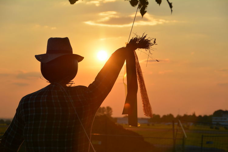 Scarecrow against sky during sunset