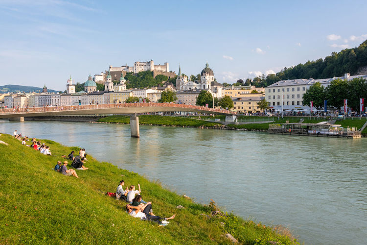 The salzburg skyline with hohensalzburg fortress and people on the bank of salzach river, austria.