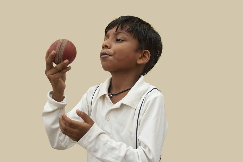 Portrait of boy holding ball against gray background