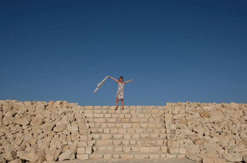 Woman with arms outstretched standing on steps against clear blue sky