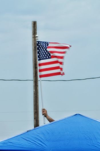 Cropped Hand Holding American Flag On Top Of Roof Against Clear Sky