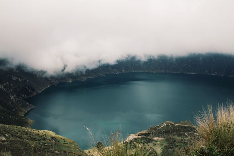 Scenic View Of Crater Lake Against Cloudy Sky
