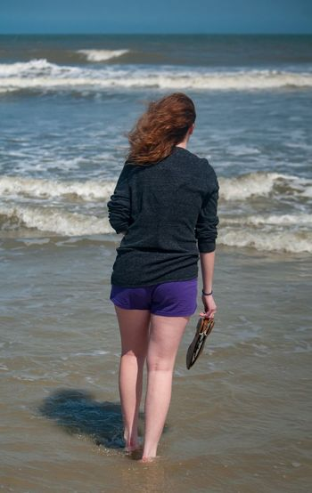 Rear view of teenage girl standing on shore in sea