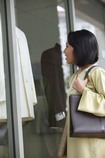 Woman looking at clothing in display cabinet