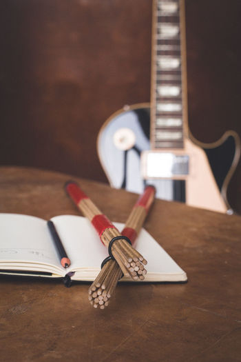 Notebook And Drumsticks On Table With Guitar In Background