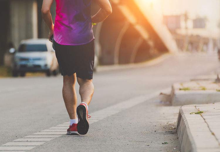 City Lifestyles Sport One Person Exercising Street Road Leisure Activity Focus On Foreground Healthy Lifestyle Sunlight Rear View Human Leg Real People Adult Running Transportation Day Women Sports Clothing Outdoors Lens Flare Human Limb Running Jogging