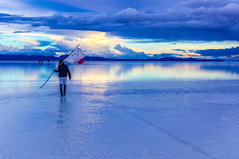 Rear view of man holding fishing net while walking at salar de uyuni against sky during sunset