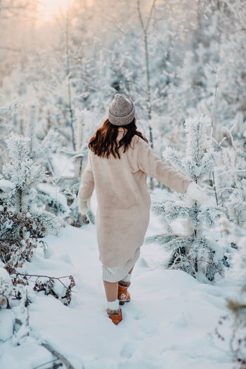 Rear view of woman standing on snow covered land